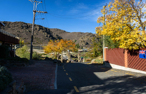 bridge autumn trees newzealand sky people signs landscape artwork rocks shadows flag hills autumncolours alexandra walkway southisland centralotago autumncolour tripdownsouth manuherikiariver historicalsuspensionbridge shakybirdge