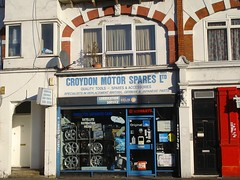 "A ground-floor shopfront seen in winter sunlight.  The sign above reads ""Croydon Motor Spares Ltd / Quality Tools — Spares & Accessories / Specialists in replacement British, German & Japanese parts"", and the full-height window is filled with wheels and boxed items.  Decorative arched brickwork can be seen on the first floor."