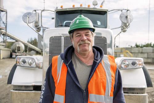 Male Truck Driver Wearing Hard Hard Standing in Front of Truck / Conducteur avec casque de chantier, debout devant son camion