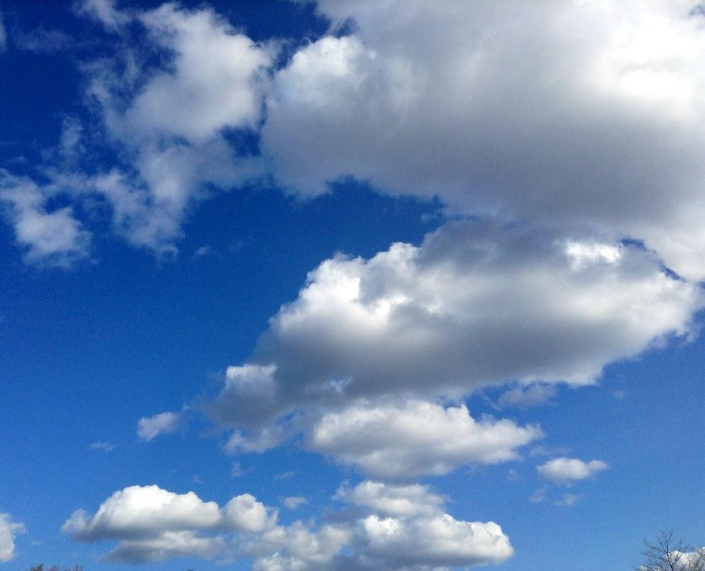 America Flag waving blue sky white puffy clouds American U