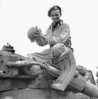 Trooper J. W. McConnell, Three Rivers Regiment, examining a knocked-out German PzKpfW III tank... / Le cavalier J. W. McConnell, du régiment de Trois Rivières, examine un char allemand PzKpfW III...