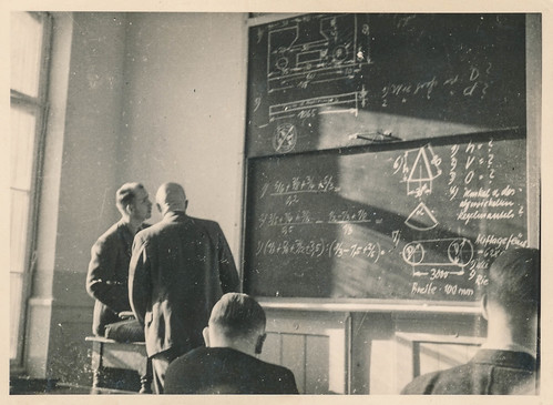 Students study an equation on a chalk board | by simpleinsomnia