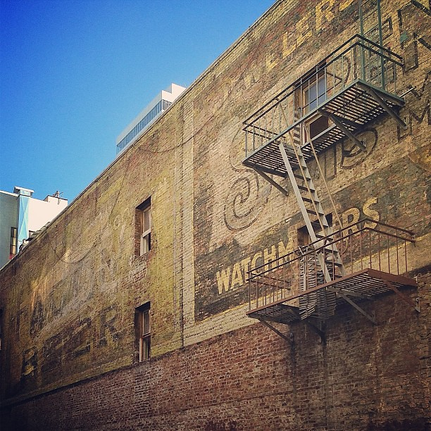 Ghost signs in San Francisco -- taken from inside the fenced-in area. Here, on the far left part of the wall, an ad for Wrigley's Spearmint Gum and an ad for beer are painted on top of each other
