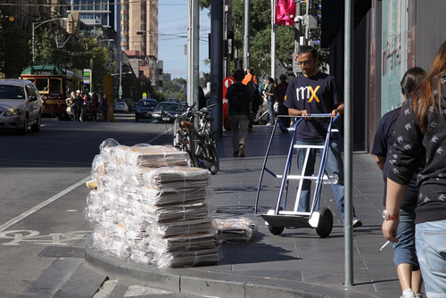 Shifting a stack of mX newspapers into Melbourne Central Station