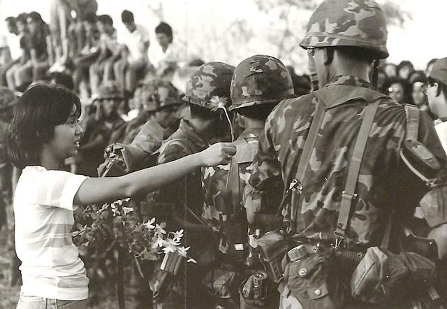 A girl gives a daisy to a Marine