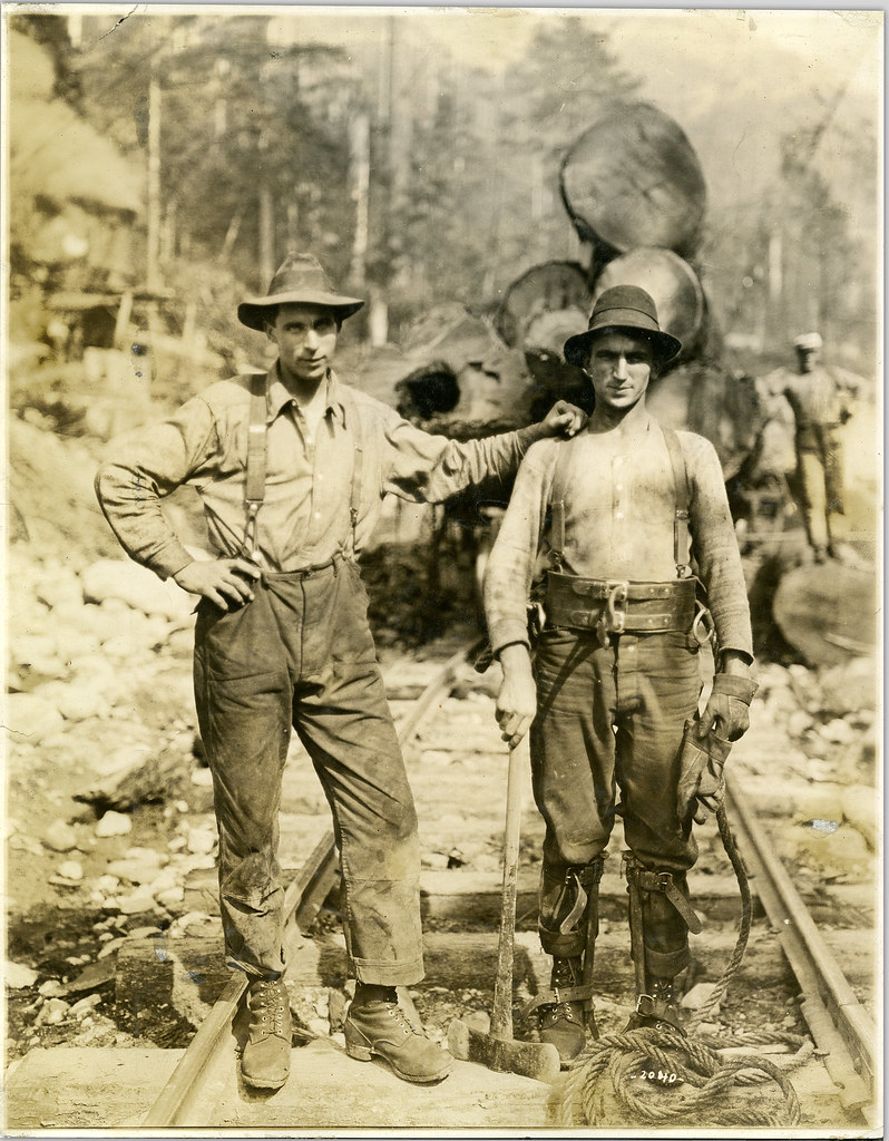 View of high rigger holding axe standing beside another employee of the Capilano Timber Company
