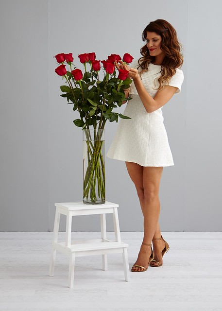 woman in white dress with giant red roses on a white stepstool