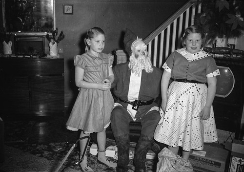 Two girls pose with a creepy Santa