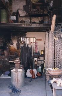 Iran - Isfahan - Iranian shop, smith having a nap