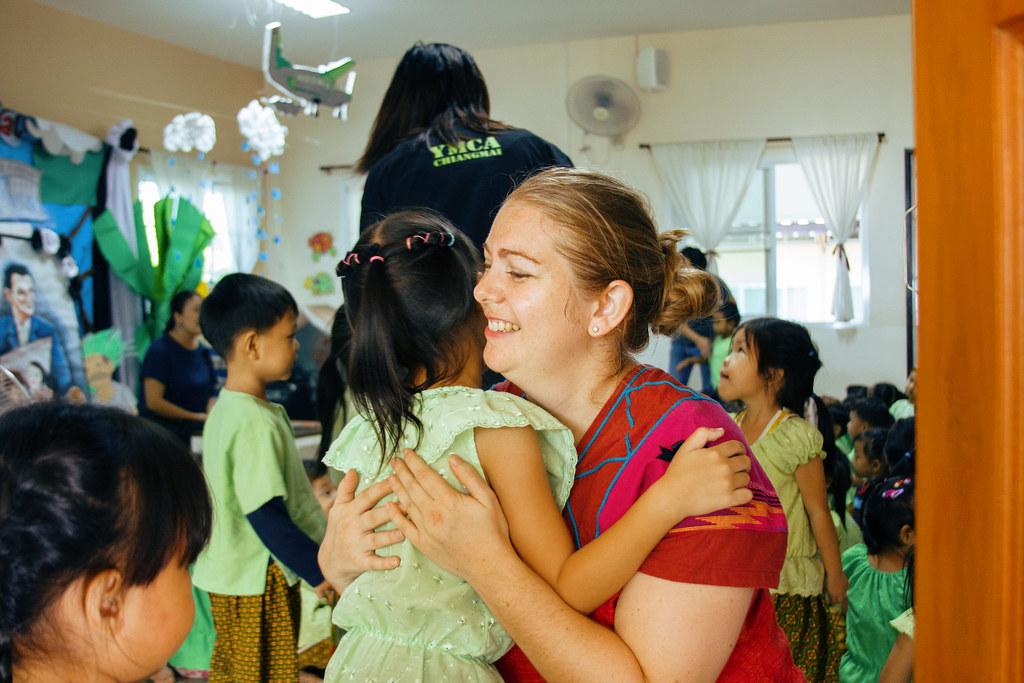 Teacher hugging young girl in classroom