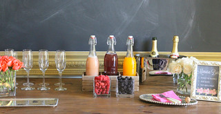 Chalkboard mimosa bar sign with orange and white flowers, champagne glasses, fruit, juice and champagne | by PersonalCreations.com
