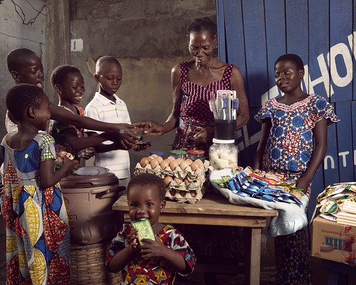 Cecile uns a makeshift grocery in the streets of Bè-Ablogamér | by World Bank Photo Collection