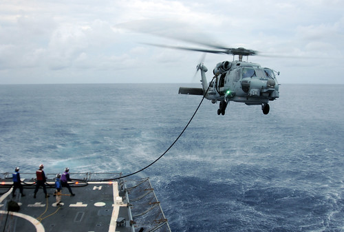 A helicopter conducts an in-flight refueling, | by Official U.S. Navy Imagery