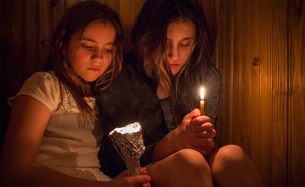 Deep Prayer | Two girls holding candles, praying in the chur