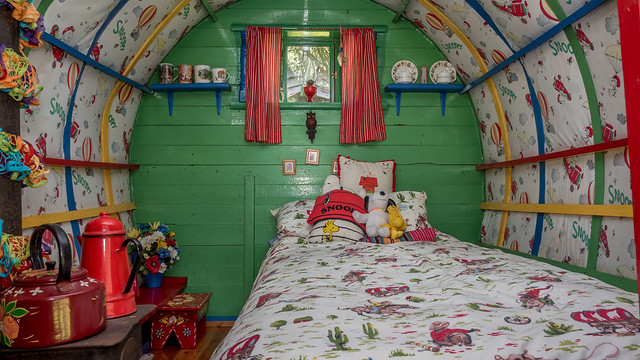 The interior of a horse-drawn bowtop gypsy caravan made into a Snoopy-themed child's bedroom