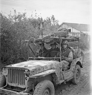 A jeep ambulance of the Royal Canadian Army Medical Corps (R.C.A.M.C.) bringing in two wounded Canadian soldiers... / Une ambulance Jeep du Corps de santé royal canadien ramène deux soldats canadiens qui ont été blessés...