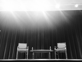 Two Chairs and Microphones on Stage Before Interview Black and White | by stevendepolo