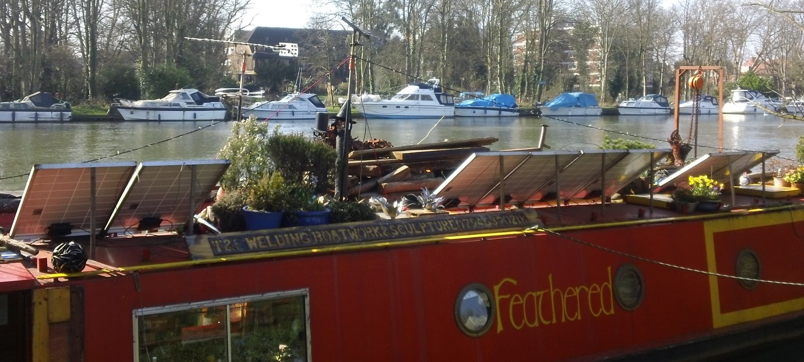 'Feathered' Thames canal boat with solar panels and rooftop garden near Kingston