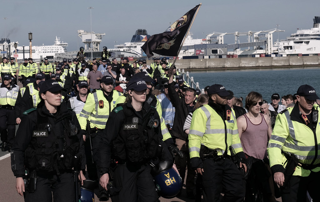 A small number of right wing anti-immigration protesters, escorted by police, take an afternoon stroll along Dover's seafront.
