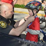June 8, 2016 - 08:50 - 'Deputy Sheriff Brian Grazidei adjusts a child's bike helmet prior to a Suffolk County Sheriff's Office Bike Rodeo in Bayport, NY.   The Suffolk County Sheriff's Office offers a Bike Rodeo and Safety Clinic to teach kids the real world skills they need to ride a bicycle safely. Lessons such as where to ride on the road, how to hand signal, how to safely cross an intersection, and how to properly wear a bicycle helmet are demonstrated and discussed by Sheriff's Officers.' Credit: Bryan Stoothoff, Suffolk County Sheriff's Office