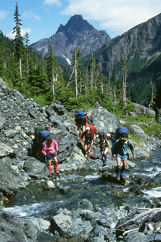 Backpack Hikers cross the Elk River in Strathcona Provincial Park on Vancouver Island, British Columbia, Canada