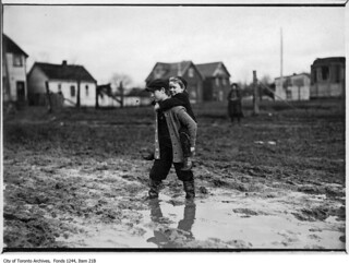 Child piggy-backing across a muddy road | by Toronto History