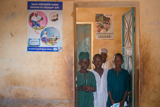 Pupils of Malikawa Garu Islamic Primary School, Bichi, Kano standing by the poster promoting the benefits of handwashing with soap in their school | by Propcom Mai-karfi