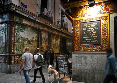 In Madrid, a street with cafes and tiled murals