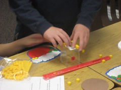 This pair of students used cubes to determine the dimensions of a rectangular prism while looking for a relationship between the dimensions and the volume of the prism. (Dec. 2010, Gr 4)