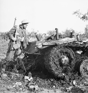 Private G. C. Butcher, 48th Highlanders of Canada, examines the wreckage of a German PzKpfw III... / Le soldat G. C. Butcher, du 48th Highlanders of Canada, examine la carcasse d'un char allemand PzKpfw III...