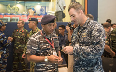 Cmdr. Greg Adams presents Letkol Laut (P) Ashari Alamsyah, commanding officer of KRI Sultan Iskandar Muda (SIM-367), with a command coin during the opening ceremony of the ASEAN Defense Minister's Meeting (ADMM) Plus Maritime Security and Counterterrorism Field Training Exercise. (U.S. Navy/MC3 Joshua Fulton)