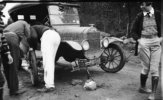 Woman watches as men change a tire on a Model T | by simpleinsomnia