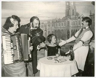 Elizabeth Connelly, TWA air hostess froom New York serenaded by head waiter with Mr & Mrs George Miller playing the violin and accordion respectively, Music Hall Restaurant, Apr 1965