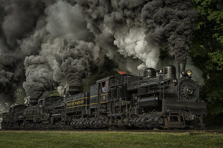Three Shay Steam Engines full throttle with massive coal smoke filling the air