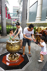 Family purifying with holy water at the Erawan Shrine