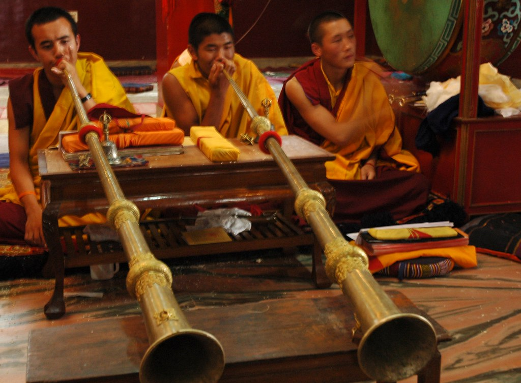 Two Tibetan Buddhist monks blowing long Tibetan Horns, while a monk beats the large green leather drum at the concluding prayers of Sakya Lamdre, Tharlam Monastery of Tibetan Buddhism, Boudha, Kathmandu, Nepal