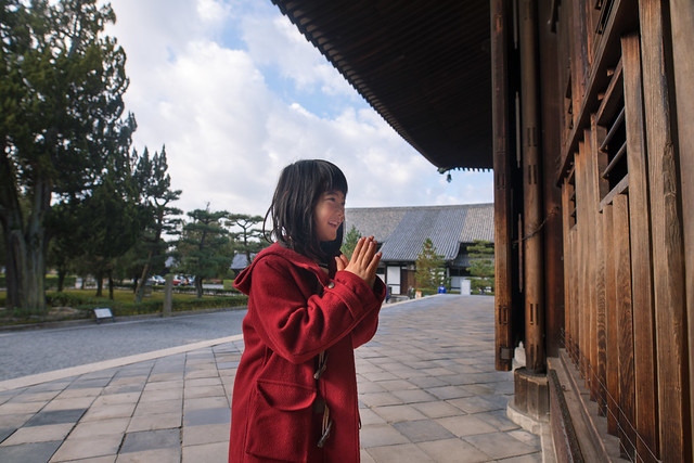 Young girl praying for peace in Tofukuji temple, Kyoto