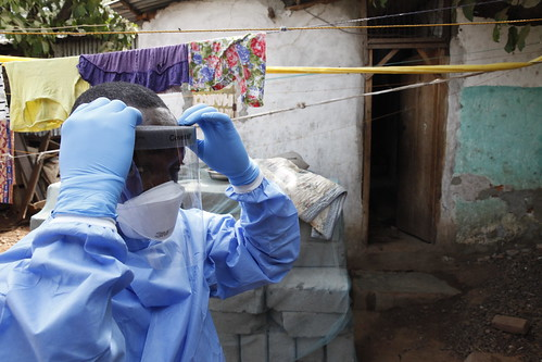 A worker for the ministry of health prepares to enter a house with protective clothing   by World Bank Photo Collection