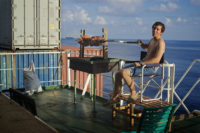 Marine officer roasting a pig on the deck of a freighter boat, Indian Ocean