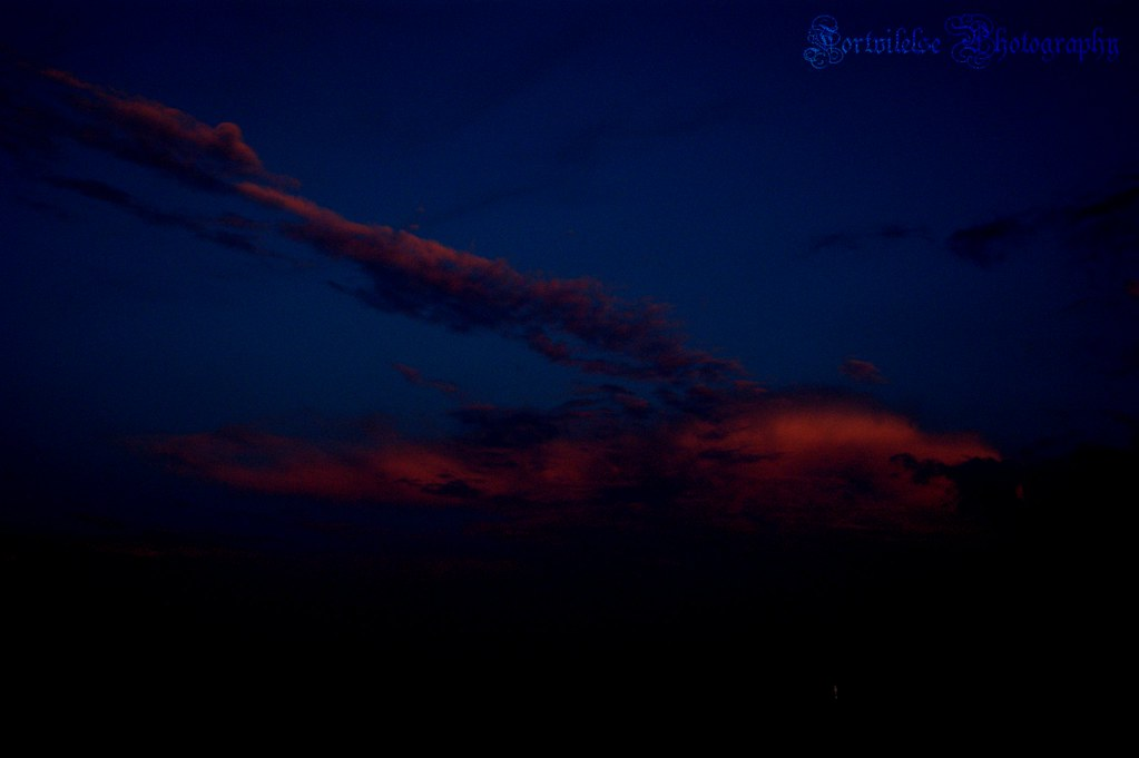 A moonless night sky with dark reddish clouds