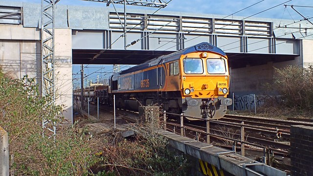 66735 propelling half a train of ballast northwards,  at Rye House, Hoddesdon, under Essex Road Bridge. 25 01 2014