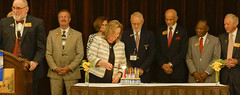 Rusine lighting the birthday candles for The Rotary Foundation's 100th.