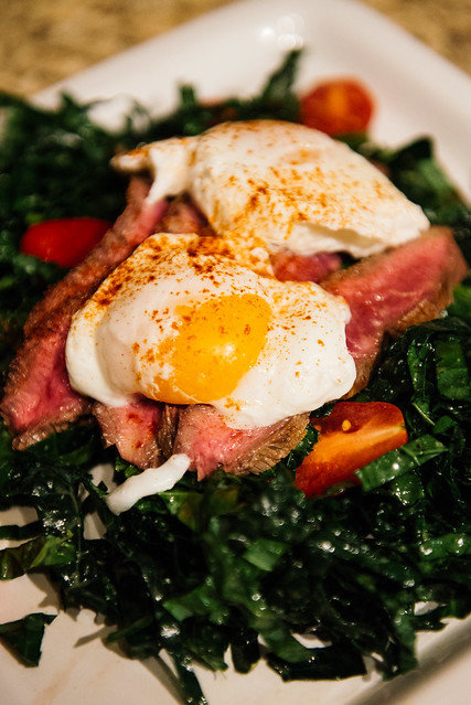 Kale salad with bacon fat vinaigrette, flat iron steak, and poached farm-fresh organic eggs
