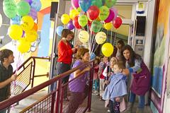 En la imagen se puede ver a Isabel Prieto y personal de la Oficina Técnica del Ayuntamiento de Ermua repartiendo los globos a los niños y niñas mientras salen del colegio
