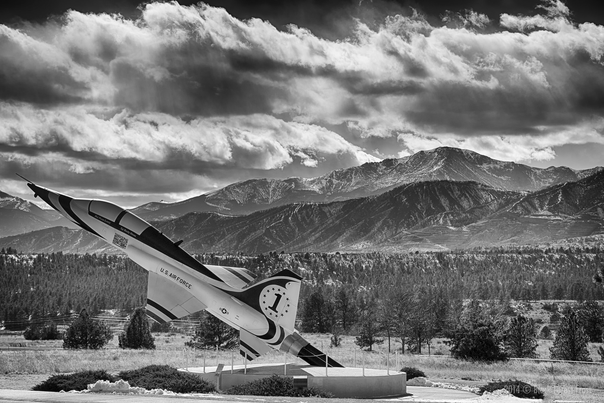 Black and white image of a military aircraft mounted on a static display pointing toward the sky, with Pike's Peak in the background