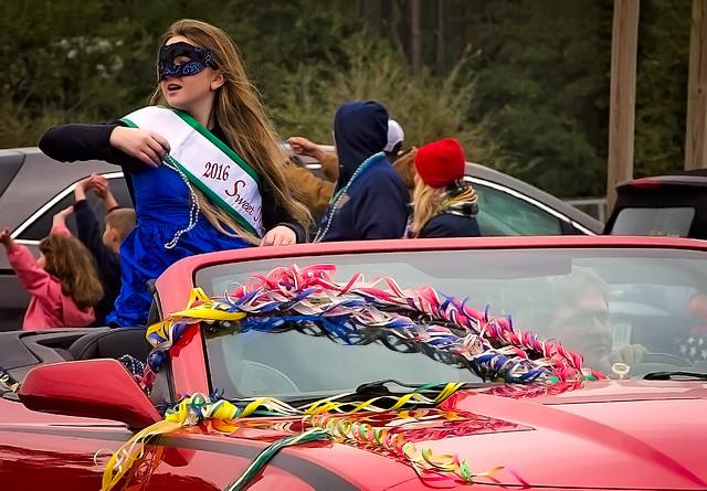 Sweet Miss Dauphin Island throws beads during the Krewe de la Dauphine Mardi Gras Parade