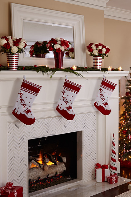 a fireplace mantel decorated with personalized stockings and three glass vases of flowers in front of a mirror hanging on the wall