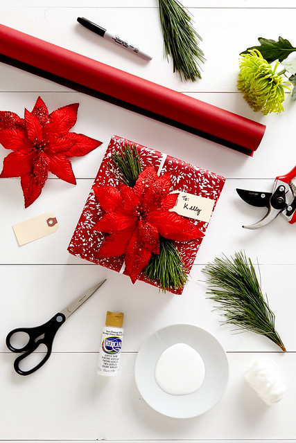 gift wrapped present with red wrapping a poinsettia bow and pine clipping with fake snow paint with scissors supplies for making it on a white table
