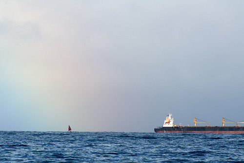 Offshore rainbow with barge and sailboat | by Navona