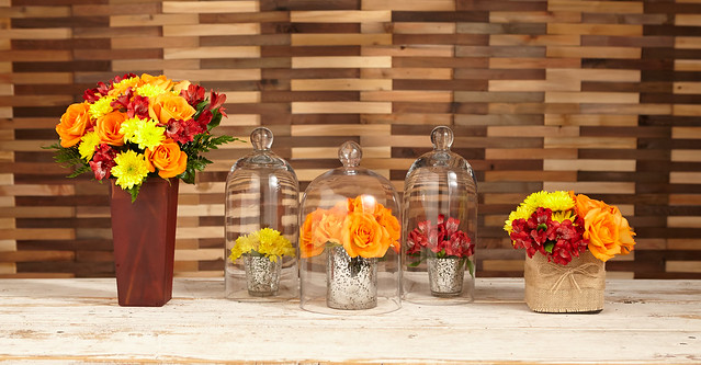 Three different ways to display orange roses red alstroemeria Peruvian lilies and yellow viking poms on a table including a tall orange vase, bell shaped glass and a canvas burlap short vase